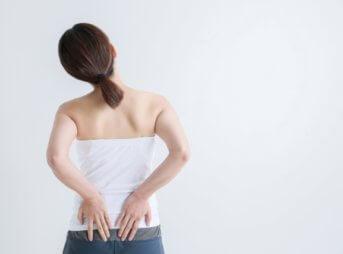 腰を抑える女性背面