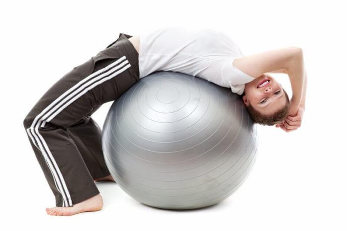 バランスボールに寝転ぶ女性
